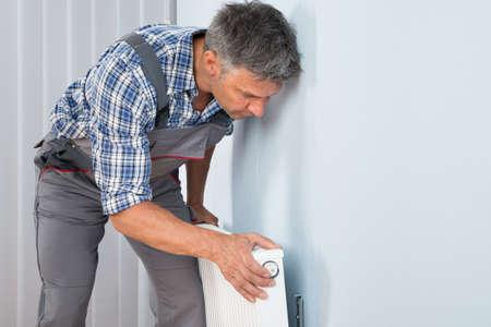 Portrait Of Male Plumber Fixing Radiator On Wall