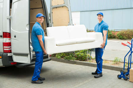 Photo pour Two Happy Male Workers Putting Furniture And Boxes In Truck - image libre de droit