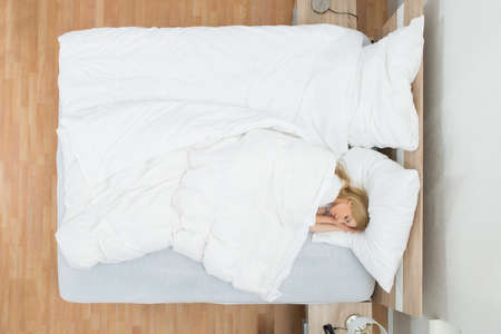Photo pour High Angle View Of Young Woman Sleeping In Bed With Blanket - image libre de droit