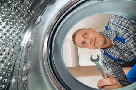 Photo pour Young Repairman With Spanner Looking Inside The Washing Machine - image libre de droit