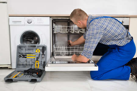 Photo pour Young Man In Overall With Toolbox Repairing Dishwasher - image libre de droit