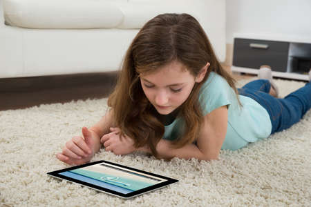Photo pour Girl Lying On Carpet Watching Video On Digital Tablet In Living Room - image libre de droit