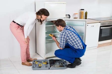 Photo pour Beautiful Housewife Looking At Male Worker Repairing Refrigerator In Kitchen Room - image libre de droit