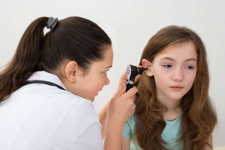 Female Doctor Examining Patient Ear With Otoscope In Clinic