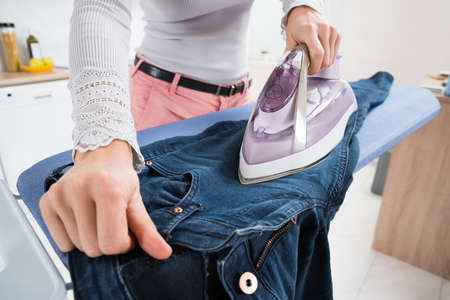 Close-up Of Woman Ironing Jeans On Ironing Board