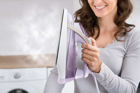 Close-up Of Woman Smiling While Holding Steam Iron In Hands