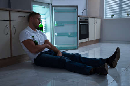 Young Man Sleeping With Beer Bottle In Kitchen