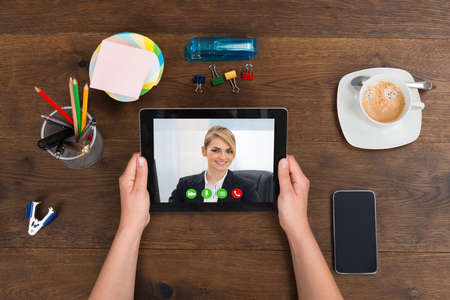Photo pour Person Videochatting With Businesswoman On Digital Tablet - image libre de droit