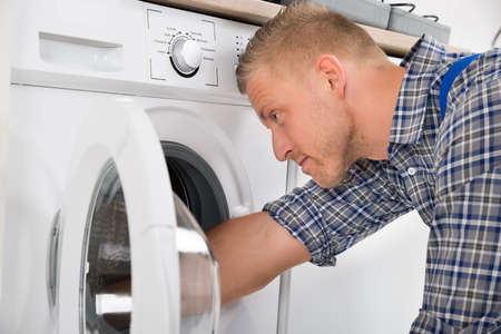 Photo for Close-up Of Professional Handyman In Overall Repairing Washing Machine - Royalty Free Image