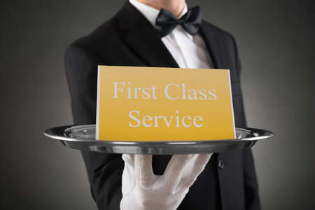 Photo pour Close-up Of Waiter Wearing Glove Giving Plate With The Text First Class Service On Board - image libre de droit