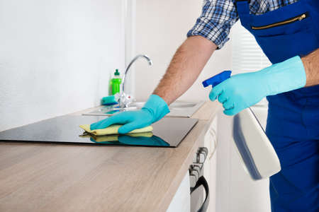 Close-up Of Worker Cleaning Electric Hob At The Countertop With Cloth