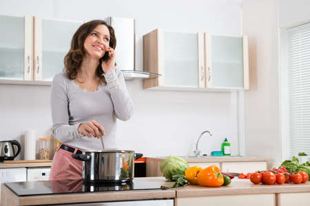 Happy Woman Talking On Mobile Phone While Cooking In Kitchen