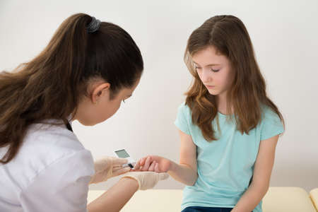 Doctor In Labcoat Measuring Blood Sugar Level Of Girl With Glucometer