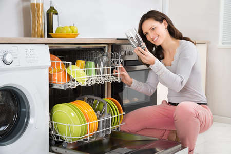 Young Beautiful Woman Taking Drinking Glass From Dishwasher In Kitchen