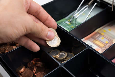 Close-up Of Person Hands Putting Coins In Cash Register