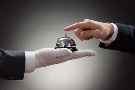 Foto für Close-up Of A Person's Hand Ringing Service Bell Hold By Waiter - Lizenzfreies Bild