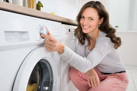 Photo for Close-up Of Young Woman Pressing Button Of Washing Machine In Kitchen - Royalty Free Image