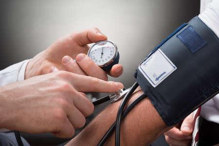 Photo pour Close-up Of A Doctor's Hand Checking Blood Pressure Of A Patient - image libre de droit