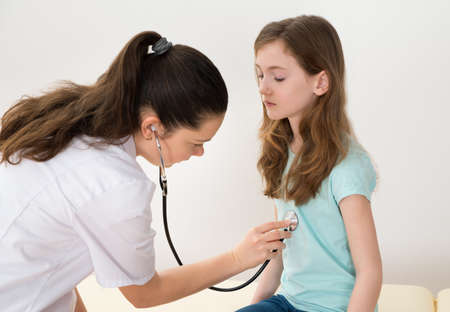Young Female Doctor Examining Girl With Stethoscope In Hospital