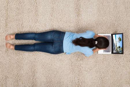 Photo pour Young Woman Lying On Carpet While Looking At Photo On Laptop - image libre de droit