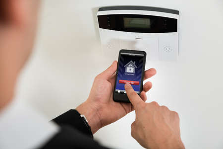 Close-up Of Businessperson Hands Disarming Security System Of Door With Mobile Phone