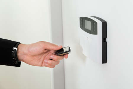 Close-up Of Businessperson Hands Operating Entrance Security System With Remote Control