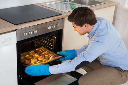 Photo pour Young Man Taking Baking Tray With Baked Bread From Oven In Kitchen - image libre de droit