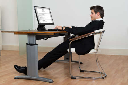 Businessman Leaning Back In His Chair While Working On Computer In Modern Office