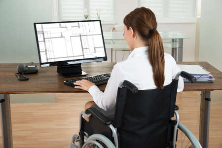 Photo pour Young Female Architect On Wheelchair Looking At Blueprint On Computer In Office - image libre de droit