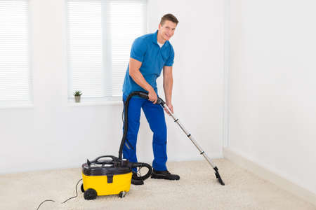 Happy Male Janitor Cleaning Carpet With Vacuum Cleaner
