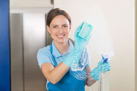 Photo for Young Happy Female Janitor Cleaning Glass With Detergent Spray Bottle And Sponge - Royalty Free Image
