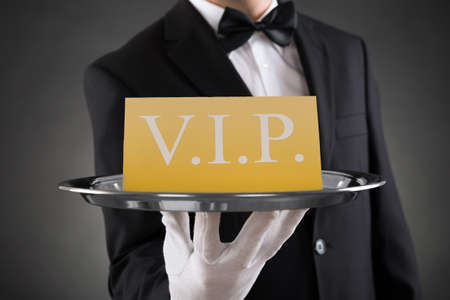 Close-up Of Waiter Showing Vip Text On Banner