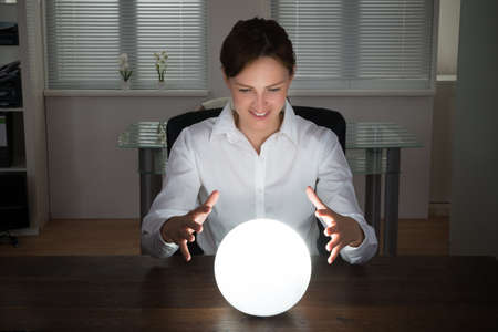 Young Businesswoman Looking Into The Future In A Crystal Ball In Office