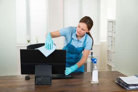 Young Woman In Workwear Rubbing Desktop Computer In Office