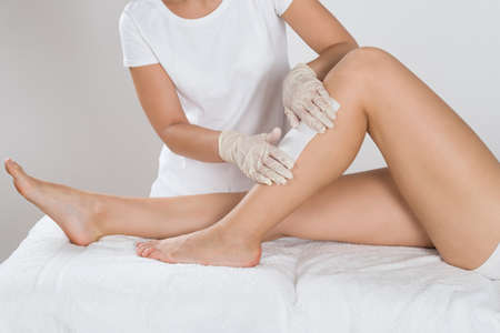 Photo pour Beautician Waxing Leg Of Woman With Wax Strip At Beauty Clinic - image libre de droit