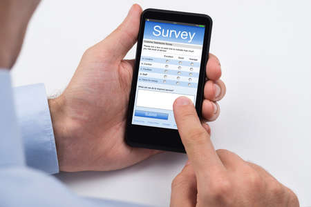 Photo pour Close-up Of Person Filling Online Survey Form On Mobile Phone - image libre de droit