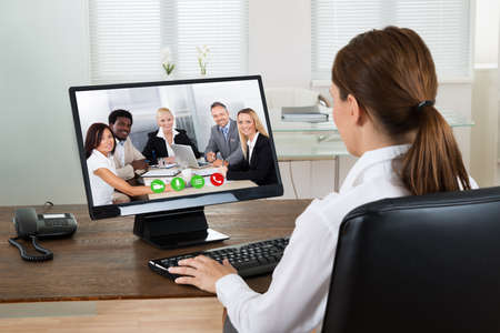 Young Businesswoman Videochatting With Colleagues On Computer In Office