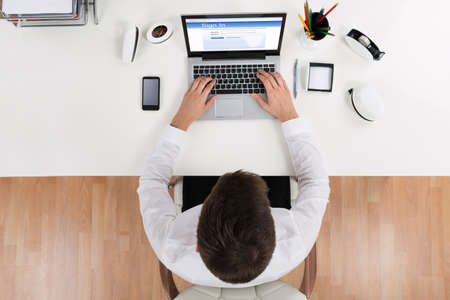 High Angle View Of Businessman Doing Login Of Online Account Using Laptop