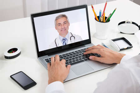 Photo pour Close-up Of Businessperson Videochatting With Doctor On Laptop At Desk - image libre de droit