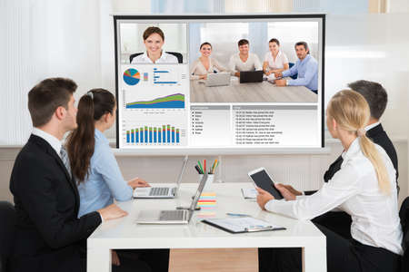Photo pour Group Of Businesspeople Attending Video Conference In Office - image libre de droit