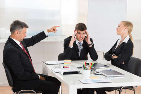 Mature Businessman Arguing With His Two Co-workers In Office