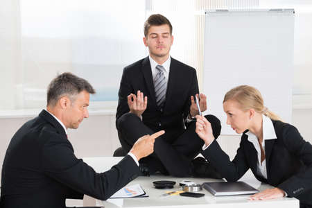 Two Businesspeople Quarreling In Front Of Businessman Meditating At Desk
