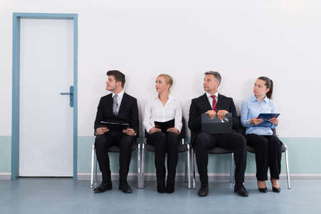 Group Of Businesspeople With Files Sitting On Chair For Giving Interview