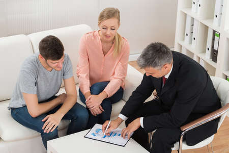 Mature Financial Advisor Showing Graph On Paper To Young Couple