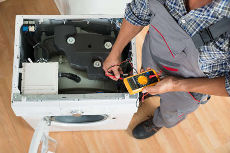 High angle view of technician checking washing machine with digital multimeter in kitchen