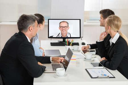 Foto de Team Of Businesspeople Videoconferencing With Doctors On Computer In Office - Imagen libre de derechos