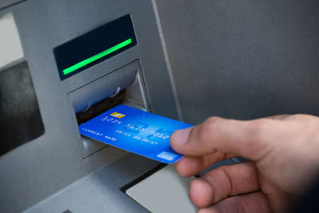 Photo pour Man's Hand Using Card To Withdraw Money - image libre de droit