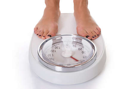 Foto de Low section of woman standing on weighing scale over white background - Imagen libre de derechos