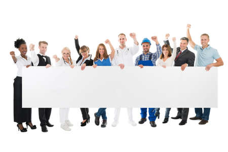 Group portrait of people with various occupations cheering while holding blank billboard against white background