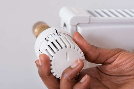 Close-up Of Person's Hand Holding Radiator Thermostat